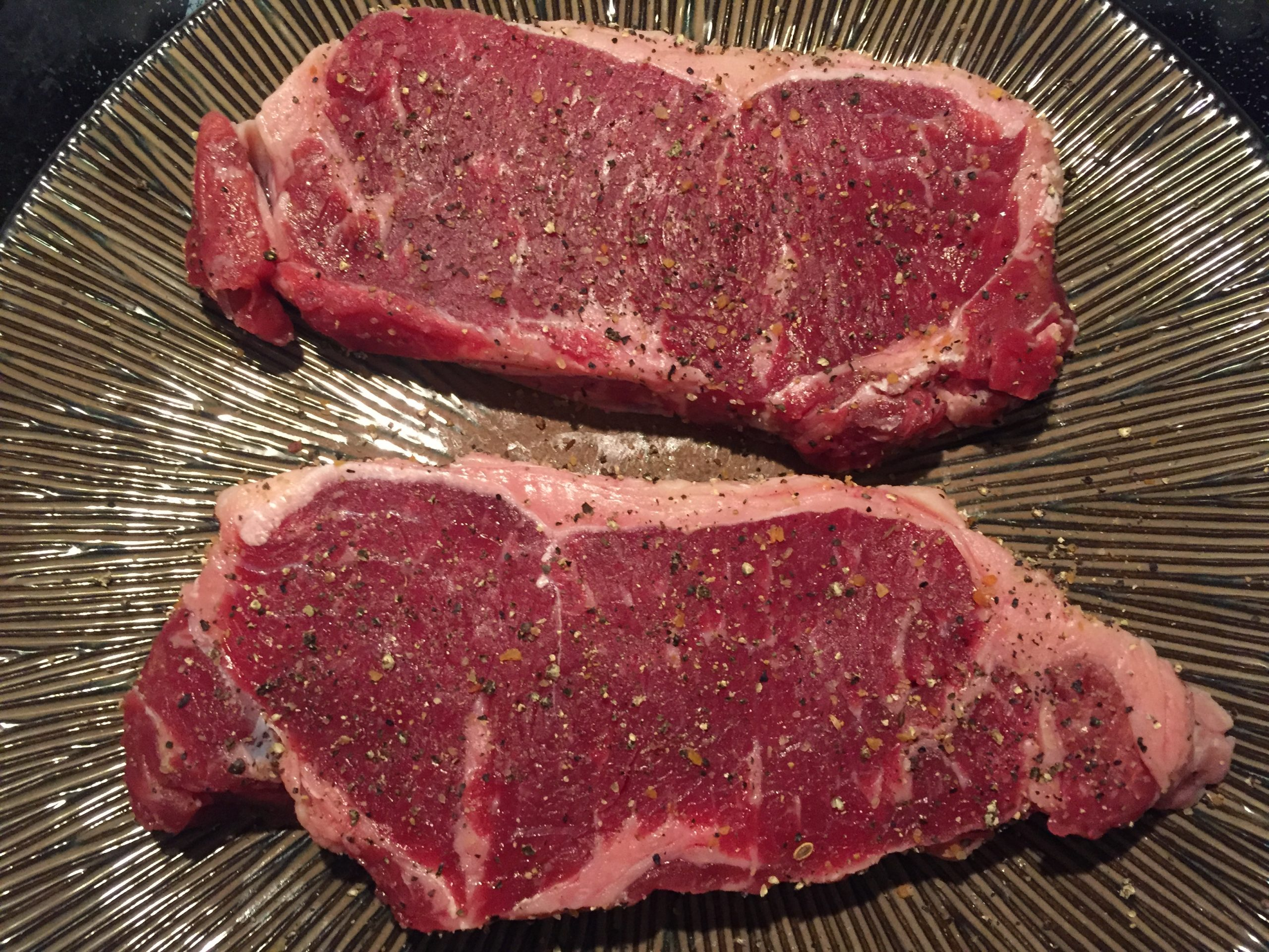 Salting Steaks Before Grilling, Seasoned With Pepper